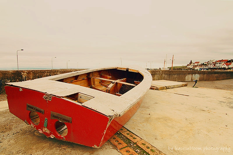 this is an image of a red boat at  East Neuk Harbour - it looks as if it has eyes and eyelashes - East Neuk photography